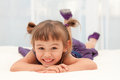 Smiling little girl lying on stomach on white bed cute caucasians asian lies tummy a child wears a purple sleeveless dress and has Royalty Free Stock Photo