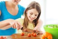Smiling little girl with mother chopping tomatoes family child cooking and home concept in the kitchen Stock Photography