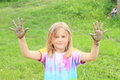 Smiling little girl with muddy hands portrait of a in colorful t shirt both dirty from mud Royalty Free Stock Photos