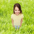 Smiling little girl over green grass background Royalty Free Stock Photo