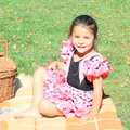 Smiling little girl on picnic in pink dress with black dots sitting brown blanket with basket Royalty Free Stock Photos