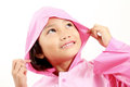 Smiling little girl pink raincoat looking upward close up Royalty Free Stock Image