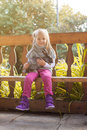 Smiling little girl posing in arbor with rabbit close up Stock Photo