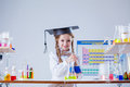 Smiling little girl posing in graduate hat at lab laboratory Stock Photo