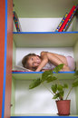 Smiling little girl reading a book on a chelf in a bookcase Royalty Free Stock Photography