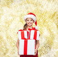 Smiling little girl in santa helper hat with gifts holidays presents christmas childhood and people concept gift boxes over yellow Stock Image