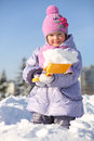 Smiling little girl with shovel shows snow in snowdrift at winter Stock Images