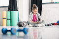 Smiling little girl sitting on floor and exercising with dumbbells in gym Royalty Free Stock Photo
