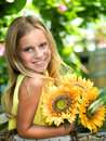 Smiling little girl with sunflower in the garden Royalty Free Stock Image