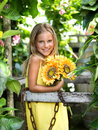 Smiling little girl with sunflower in garden Stock Images
