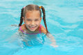 Smiling little girl swims in pool Royalty Free Stock Image