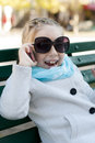 Smiling little girl in talking on cell phone the with glasses Stock Photos