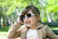 Smiling little girl in talking on cell phone the park with glasses Stock Images