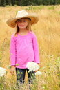 Smiling little girl wearing straw western hat.