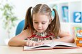 Smiling little student girl reading book Royalty Free Stock Photo