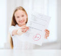 Smiling little student girl with test and a grade education school concept at school showing thumbs up Stock Photo