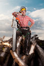 Smiling lumberjack with chainsaw man beautiful natural sky on background Royalty Free Stock Photo