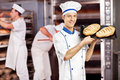 Smiling male baker posing with freshly baked breads in bakery while others working Stock Image