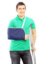 Smiling male with broken arm and crutch isolated on white background Stock Photos