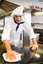 Smiling male cook wiping the counter top in kitchen Royalty Free Stock Photo