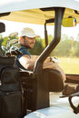 Smiling male golfer sitting in a golf cart Royalty Free Stock Photo