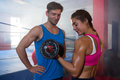 Smiling male looking at female athlete lifting dumbbell Royalty Free Stock Photo