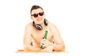 Smiling male lying on a beach towel and drinking cold beer isolated white background Royalty Free Stock Photos