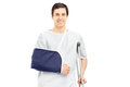 Smiling male patient in hospital gown with broken arm holding a crutch isolated on white background Stock Photography