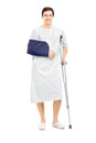 Smiling male patient in hospital gown with broken arm holding a full length portrait of crutch isolated on white background Royalty Free Stock Photo