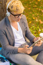 Smiling male student in eyeglasses with tablet pc education technology and internet concept and headphones outdoors Royalty Free Stock Photo