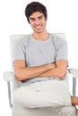 Smiling man with arms crossed sitting on a swivel chair white background Royalty Free Stock Images