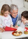 Smiling man assisting children in making greeting senior men christmas card at home Royalty Free Stock Photo