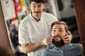 Smiling man barber is serving client men satisfied Stock Photography