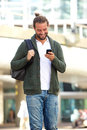 Smiling man with beard looking down at cellphone Royalty Free Stock Photo