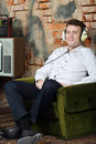 Smiling man in big headphones listens old radio and sits armchair very house Royalty Free Stock Photo
