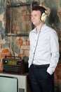 Smiling man in big headphones listens old radio very house Stock Photos