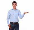 Smiling man in blue is holding his palm out shirt standing while on white background copyspace Stock Image