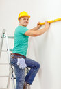 Smiling man building using spirit level to measure repair and home concept in helmet new home Stock Photography
