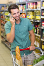 Smiling man buy food and phoning at supermatket Stock Image