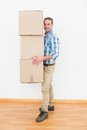 Man carrying pile of cardboard moving boxes