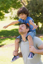 Smiling man carrying son on his shoulders in park side view of a men the Royalty Free Stock Photo