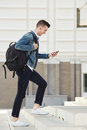 Smiling man with cellphone and headphones walking on stairs Royalty Free Stock Photo