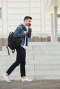 Smiling man on cellphone walking outdoors] Royalty Free Stock Photo
