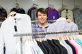 Smiling man choosing shirts in mall Royalty Free Stock Photo