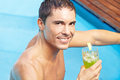 Smiling man with drink in pool Stock Photos