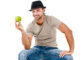 Smiling man eating an green apple young holding isolated on white background Stock Photography