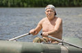 Smiling man enjoying a row in a rubber dinghy senior as he sits shirtless the boat with his hands on the oars at the Stock Photo