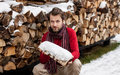 Smiling man with firewood winter countryside landscape happy forty years old caucasian outdoor in front of stacked chopped Stock Photo