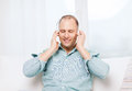 Smiling man with headphones listening to music leisure and lifestyle concept happy at home Royalty Free Stock Photos