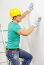 Smiling man in helmet doing renovations at home repair renovation and concept Royalty Free Stock Photos